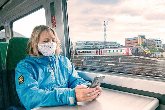 Young lady sat on train with mask (COVID) looking at phone