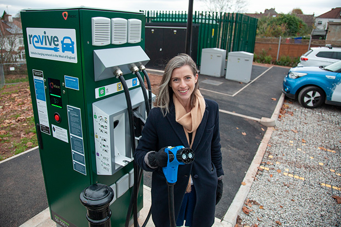 Young lady next to electric vehicle charge point holding charger