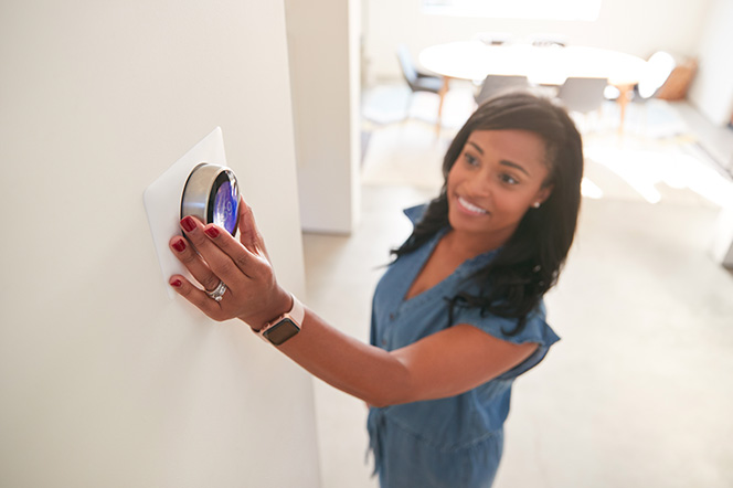 Young female turning home thermostat down