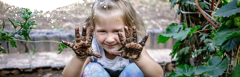 Young child showing muddy hands in the garden