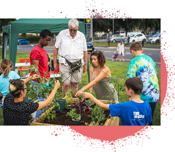 ALW group, adults and children potting plants in large wooden planter.