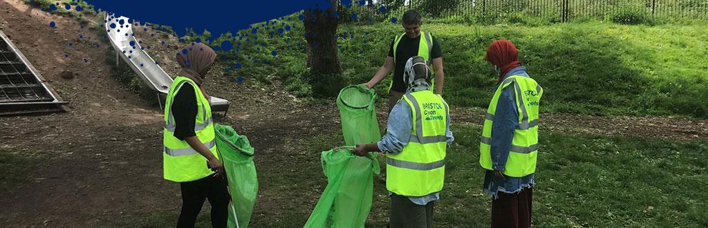4 people with hi-vis vests litter picking in Bristol park.