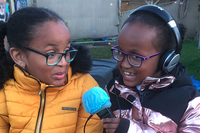 2 young sisters sat on bench, one interviewing the other.