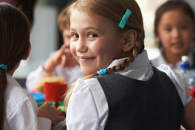 Young girl in school uniform smiling at camera